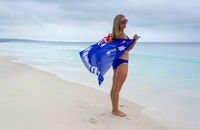 Female standing on the beach with Aussie flag in the breeze