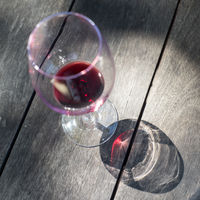 Glass of red wine on wooden background.