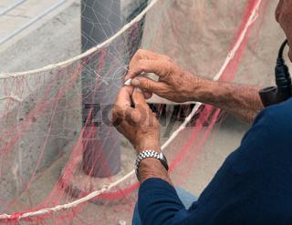 Senior fisherman reparing fishing net