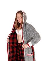 A woman in a gray bath robe and white bra in profile