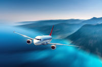 Airplane is flying over blue sea and mountains at sunset