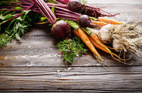 Fresh organic beetroots green garlic and carrots on kitchen wooden rustic table close up view