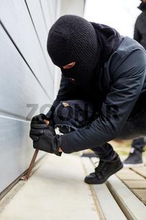 Einbrecher mit Brecheisen an Garage oder Lagerhalle