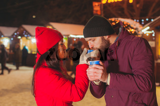 Attractive couple tasting mulled wine at Christmas market