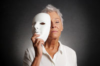 serious older woman revealing face behind mask