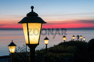 Illuminated Streetlights along Dutch boulevard with beautiful sunset over the sea