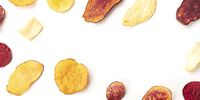 A panoramic overhead shot of dry fruit and vegetable chips, healthy vegan snack, on a white background, forming a frame for copyspace