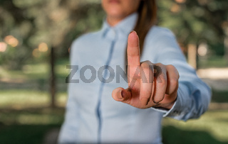 Woman in a blue business shirts pointing with her finger into empty space. Copy space with pointing finger. Business concept with woman in a shirt.