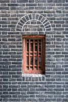 Small red window in a brick wall