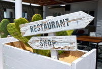 White obsolete sign board with arrows. Restaurant and shop directions. Ibiza Island. Balearic islands, Spain