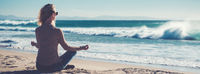 Horizontal image rear view young blond woman sitting in lotus position folded fingers mudra gesture meditating on the beach near the sea or ocean, water and clear sky copy space for ad concept text