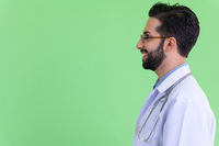 Closeup profile view of happy young bearded Persian man doctor smiling