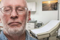 Worried Senior Adult Man Waiting in Doctor Office