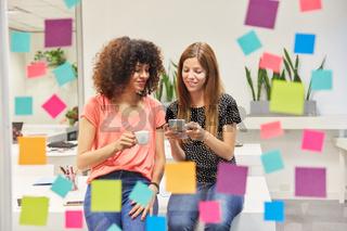 Zwei junge Business Frauen lesen zusammen eine SMS