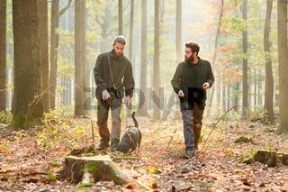Zwei Jäger mit einer Bracke als Jagdhund im Wald
