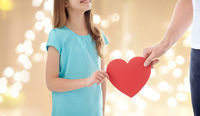 close up of girl and father hand holding red heart