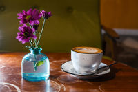 Cappuccino cup on table wih flowers in bottle