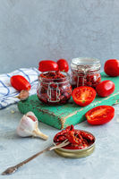 Homemade dried tomatoes in glass jars.