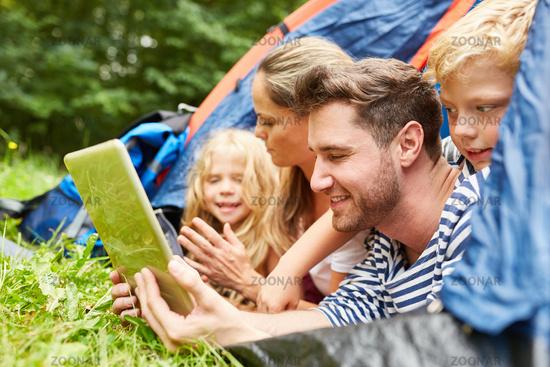 Familie im Zelt schaut auf Tablet Computer