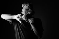 Sad young African man with teddy bear and love sign text giving thumb down