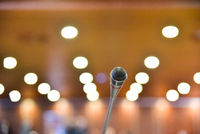 Microphone on the table of a conference room with unfocused background to communicate news, without anyone.