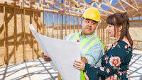 Hispanic Male Contractor Talking with Female Client Over Blueprint Plans At Construction Site