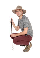 Young man crouching in safari hat