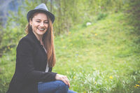 Spring: elegant young woman in hat, 20 - 30 years old, enjoys the sunshine in the garden.