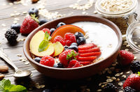 Fruit healthy muesli with peaches strawberry almonds and blackberry in clay dish with yogurt on wooden kitchen table
