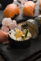 A plate of different combination of sushi with a bowl of soba