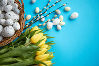 Holiday contept decoration with easter eggs and yellow tulips over blue