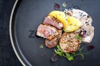 Fried pork fillet with boiled potatoes and mushrooms in cream sauce as top view on a plate with copy space left
