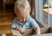 Young baby boy investigating a cardboard box and looking inside