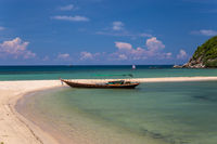 Traditional thai long boat moored at a beach