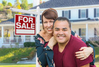 Mixed Race Young Adult Couple In Front of House and For Sale Real Estate Sign