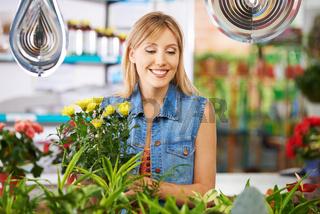 Frau kauft im Blumenladen ein