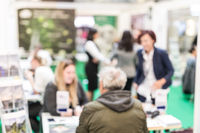 Anonymous blurred people discussing business at a trade fair.