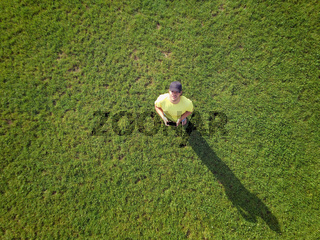 Adult young man is controlling his drone and taking some photos and videos. Aerial top view, technology and carefree lifestyle concept.