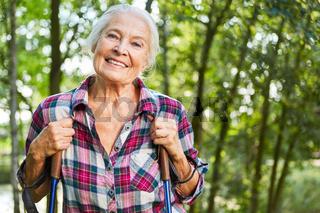 Zufrieden lächelnde Seniorin beim Nordic Walking