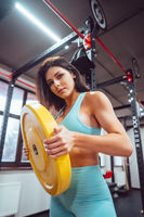 Young adult girl doing strength exercises in the gym