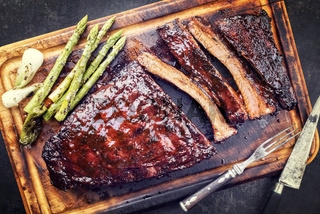 Barbecue spare ribs St Louis cut with hot honey chili marinade and green asparagus as top view on an old rustic board