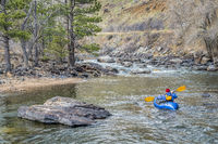 paddler in  packraft on mountain river