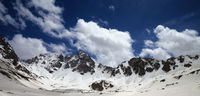 Panoramic view on high snowy mountains and blue cloudy sky