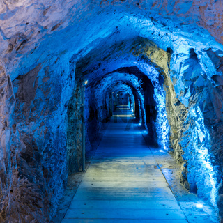 tight and narrow old tunnel leading through a mountain with blue lighting to guide the way
