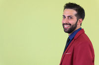 Closeup profile view of young happy bearded Persian businessman in suit looking at camera