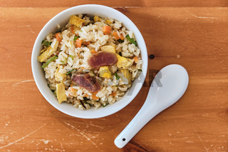 A Bowl of Chinese Fried Rice with Pork Sausages and vegetables.