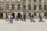 People riding scooters in front of Royal Palace and though the center of Amsterdam Netherlands