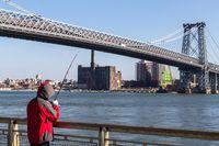 Fisherman at Williamsburg Bridge in New York City