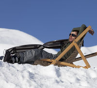Skier at winter snowy mountains resting on sun-lounger