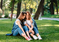 Two friends are sitting on the green lawn in the park.
